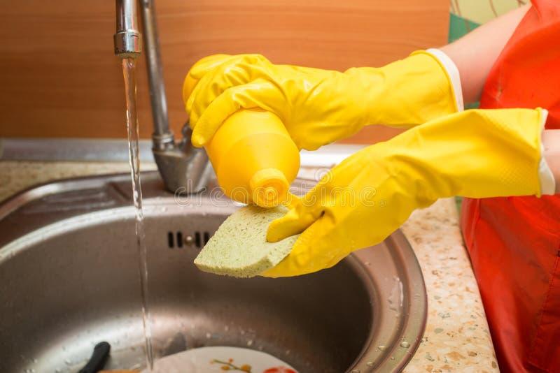 使用在海绵的妇女清洁产品在家做盘` s厨房 库存照片