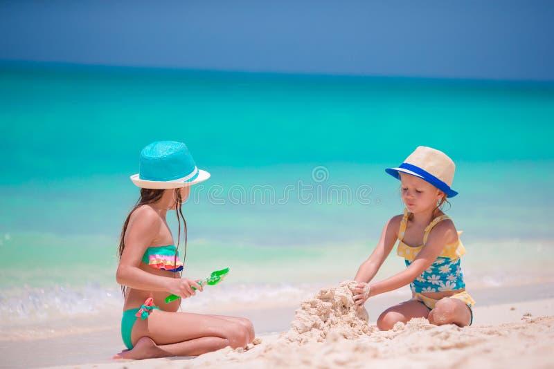 使用在海滩沙子的愉快的小女孩在热带假期时 库存照片