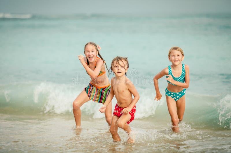 使用在海滩的三个愉快的孩子 库存照片