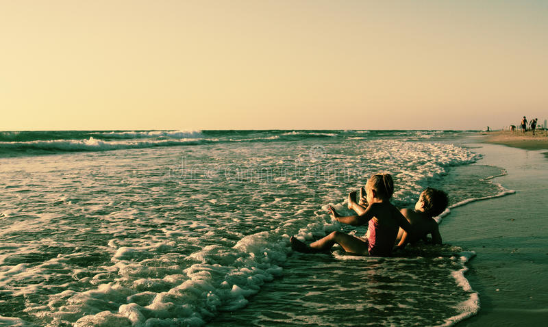 使用在海滩的两个愉快的孩子 免版税库存照片