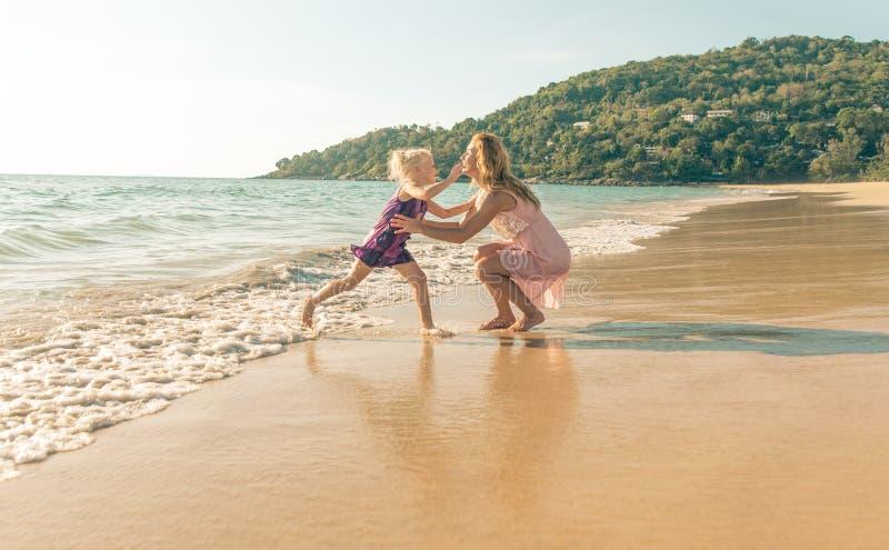 使用在海滩的妈妈和女儿 免版税图库摄影