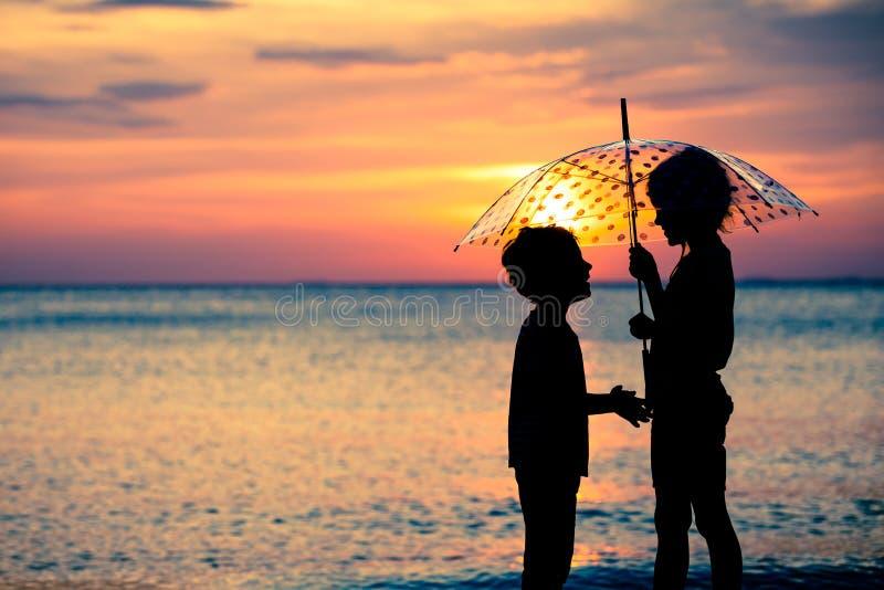 使用在海滩的愉快的孩子在日落时间 免版税库存照片