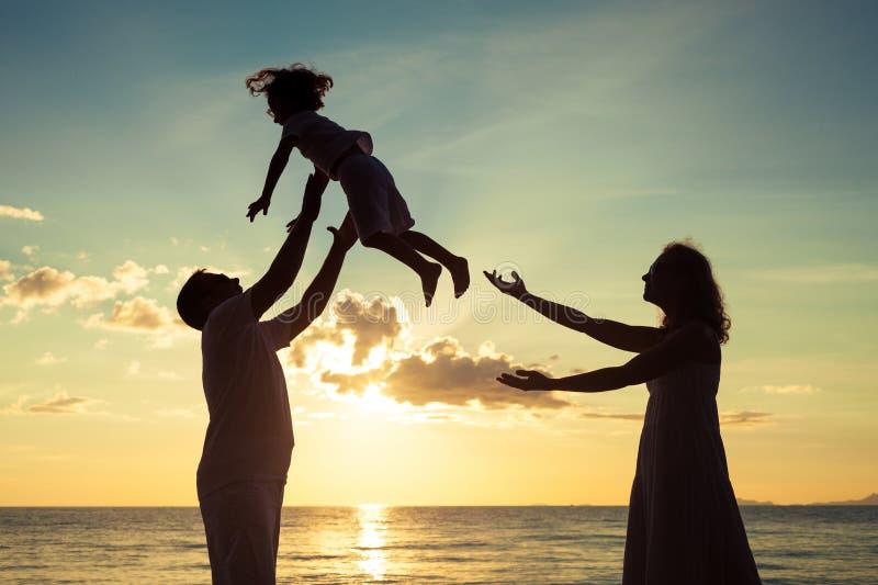 使用在海滩的愉快的家庭剪影在sunse