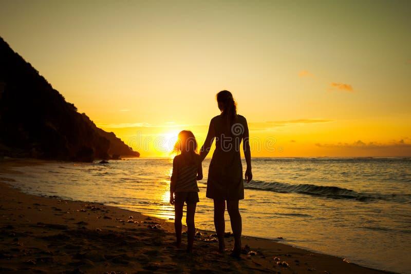 使用在海滩的母亲和女儿 免版税库存图片