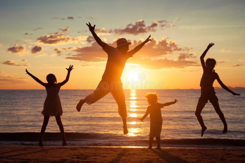 使用在海滩的父亲和孩子在日落时间 免版税库存照片