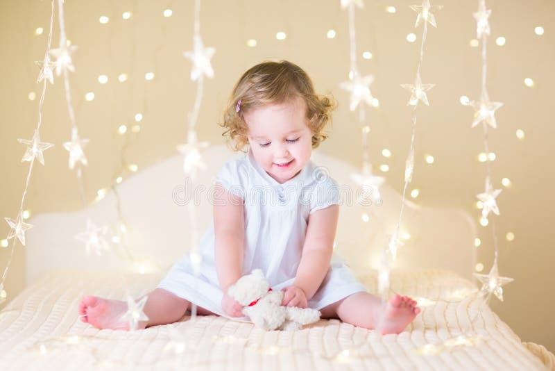 使用在温暖的软的圣诞节l之间的一张床上的美丽的小孩女孩 库存照片