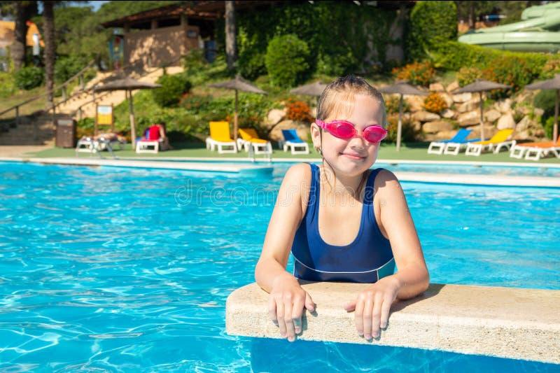 使用在游泳场海滩胜地、暑假、旅行和旅游业概念的风镜的愉快的女孩 免版税图库摄影