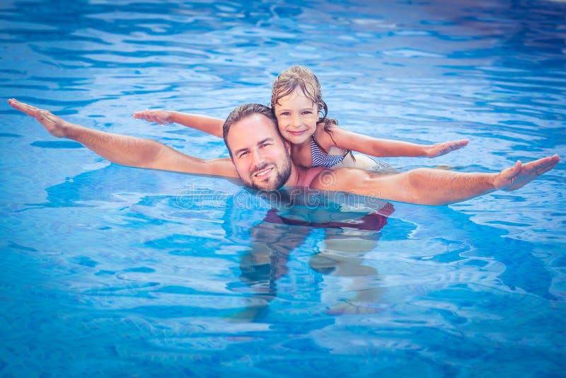 使用在游泳池的孩子和父亲 免版税库存照片