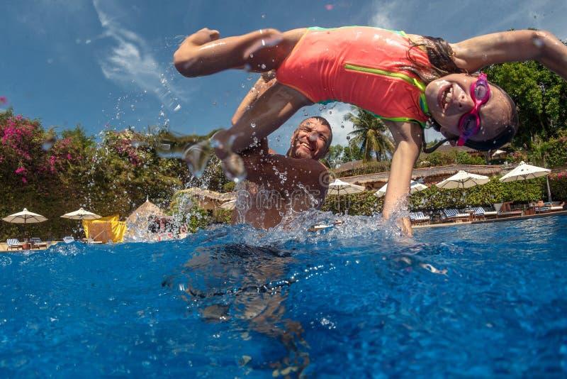 使用在游泳池的父亲和女儿 免版税库存照片