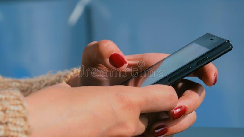 使用在游轮甲板的妇女智能手机在日落 库存照片