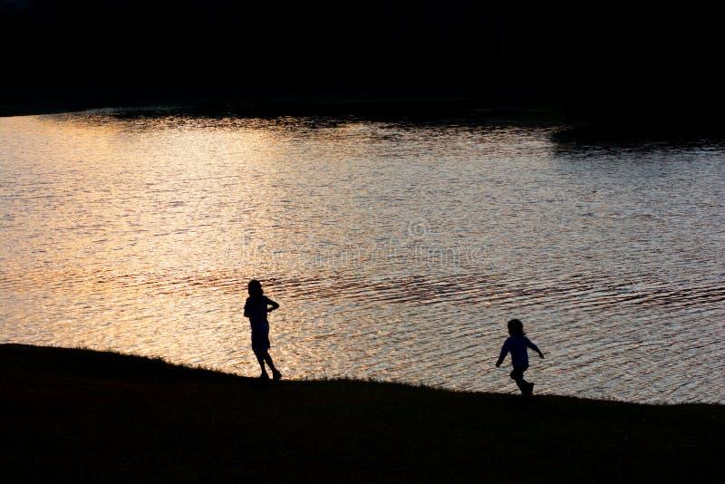 使用在湖旁边的两个孩子在日落 免版税库存照片