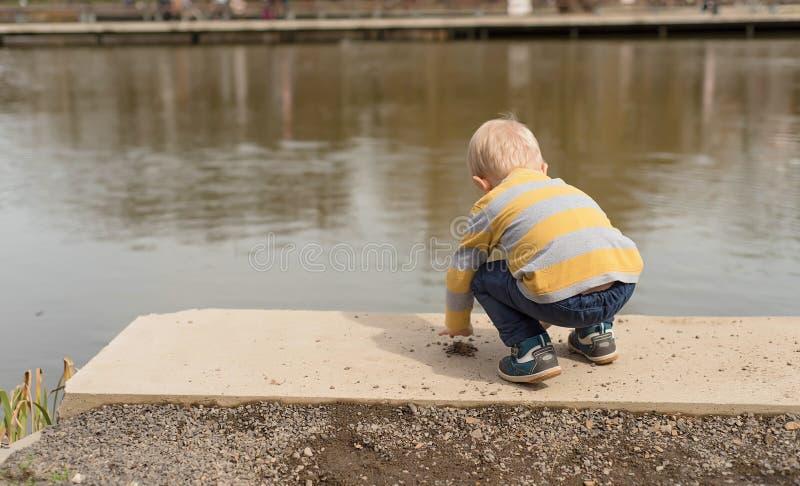使用在湖附近的小男孩 免版税库存照片