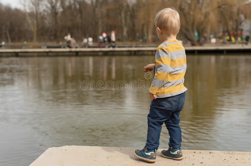 使用在湖附近的小男孩 库存照片