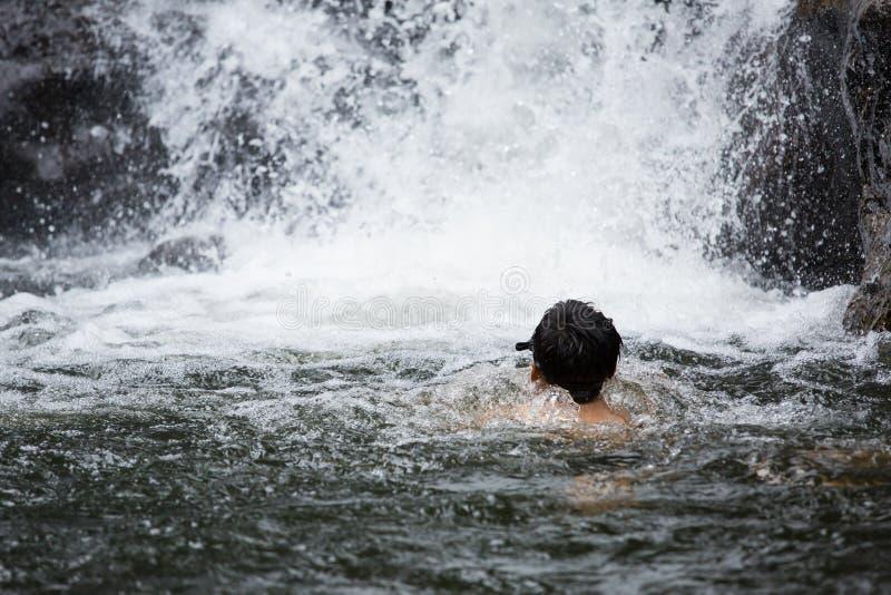 使用在瀑布中水的男孩  免版税库存图片