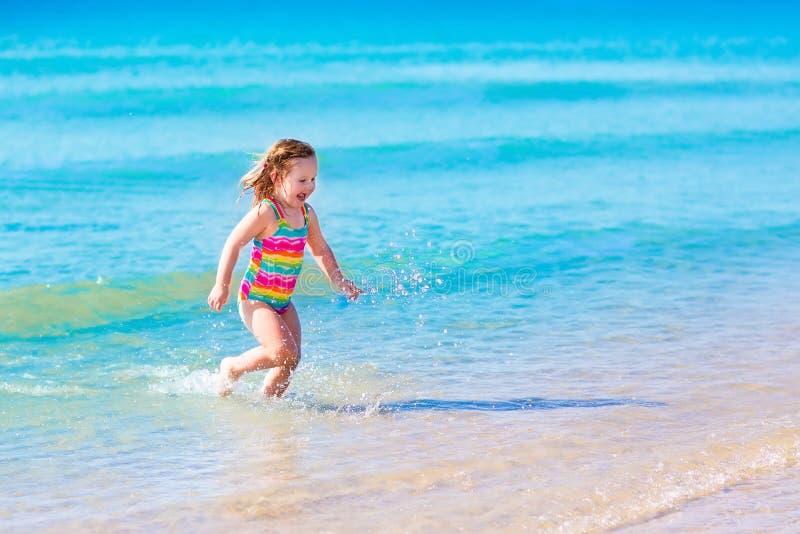 使用在热带海滩的小女孩 图库摄影