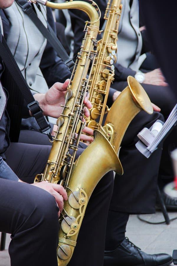 使用在爵士乐队的萨克斯管吹奏者,穿戴在人` s经典背心和长裤 图库摄影
