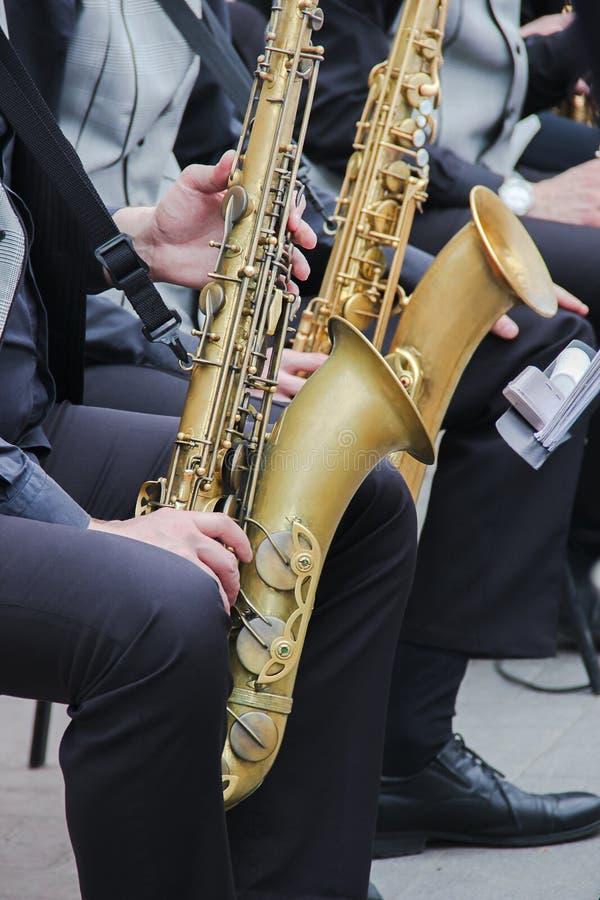 使用在爵士乐队的萨克斯管吹奏者,穿戴在men& x27; s经典背心和长裤 关闭手射击  库存照片