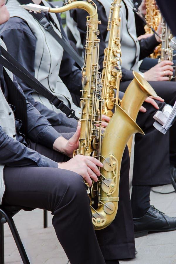 使用在爵士乐队的萨克斯管吹奏者,穿戴在men& x27; s经典背心和长裤 库存照片