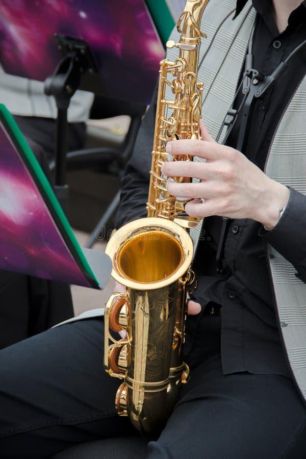 使用在爵士乐队的萨克斯管吹奏者,穿戴在men& x27; s经典背心和长裤 免版税图库摄影