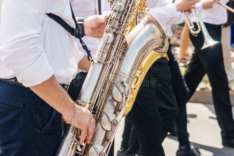 使用在爵士节的萨克斯管吹奏者在城市公园 库存照片