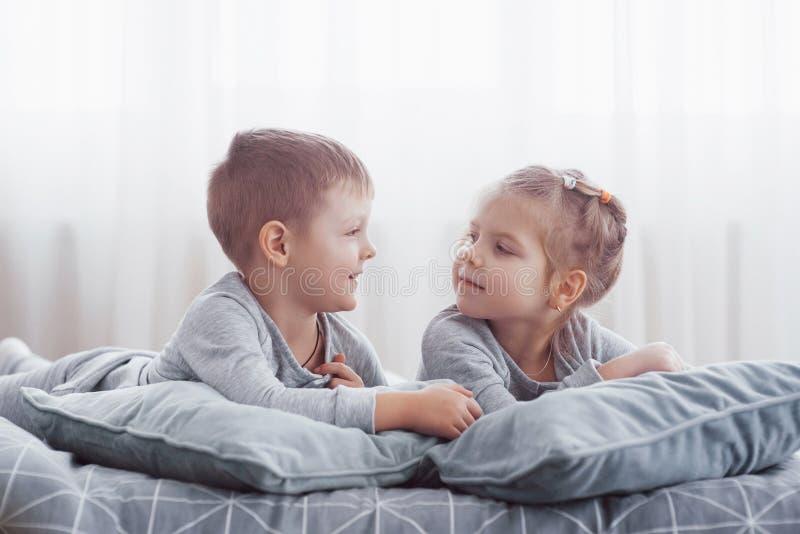 使用在父母床上的孩子 孩子在晴朗的白色卧室醒 在配比的睡衣的男孩和女孩戏剧 睡衣裤 库存图片