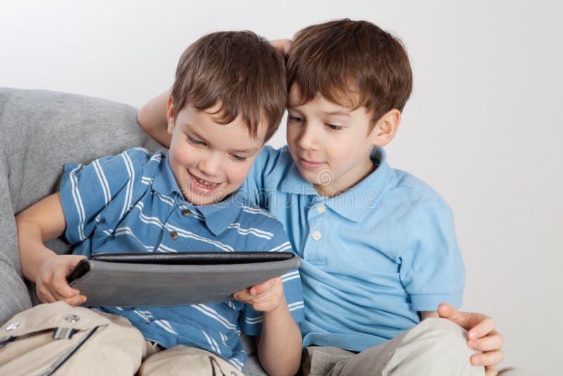 使用在片剂的二个兄弟 免版税库存照片