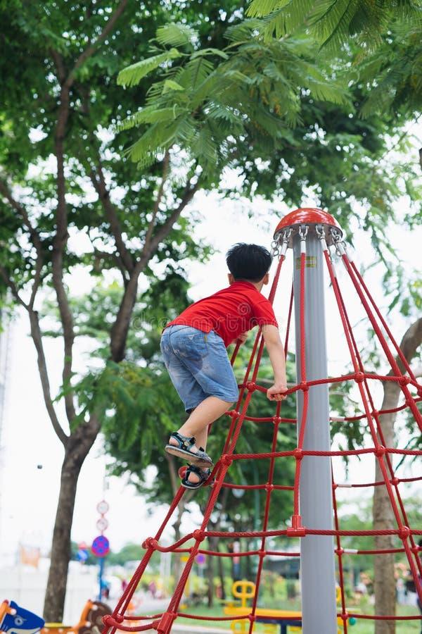使用在猴子栏杆的小男孩在操场 库存照片