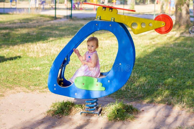 使用在玩具飞机的小女孩在操场 免版税库存照片