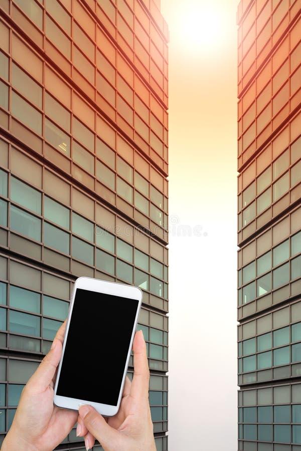 使用在现代大厦背景的巧妙的电话关闭手 免版税库存图片