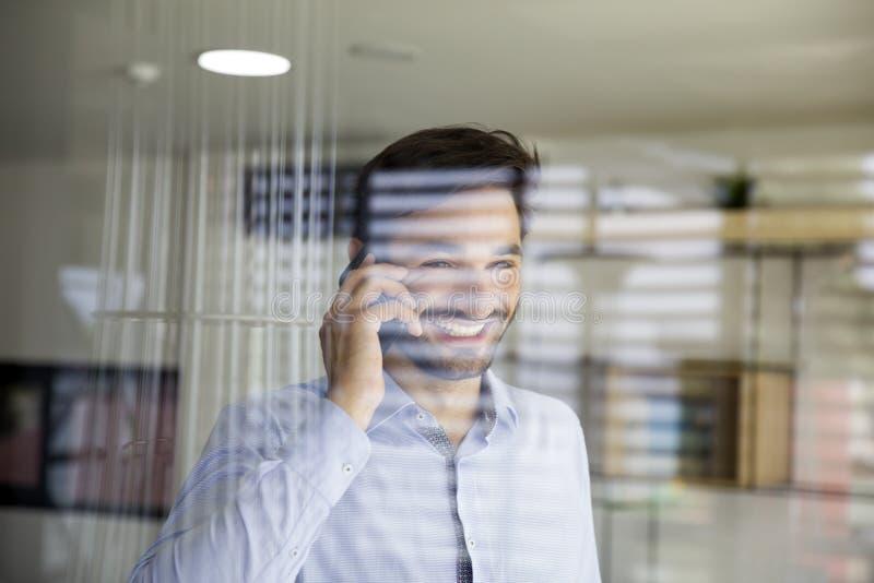 使用在玻璃后的年轻人手机在办公室 图库摄影