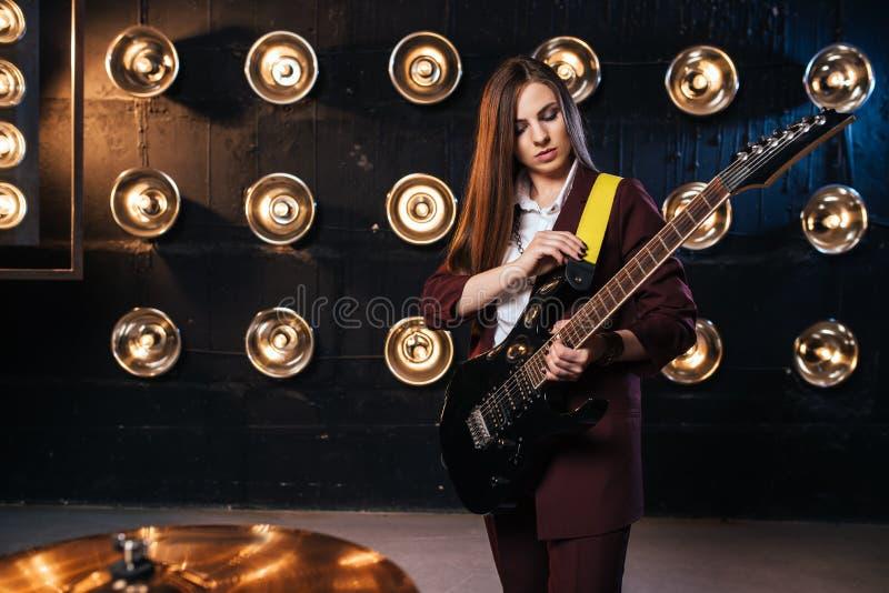 使用在电吉他的衣服的女性音乐家 免版税库存图片