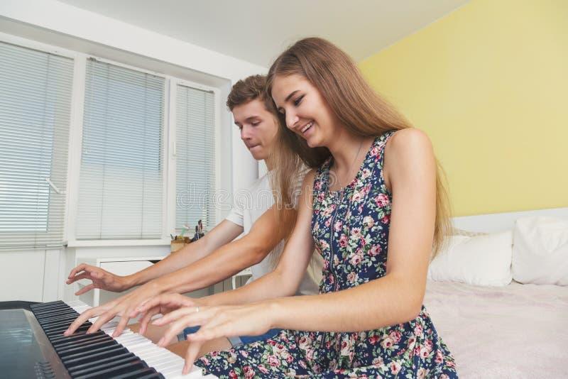 使用在电子钢琴的少年夫妇  图库摄影