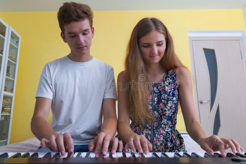 使用在电子钢琴的少年夫妇  免版税库存照片