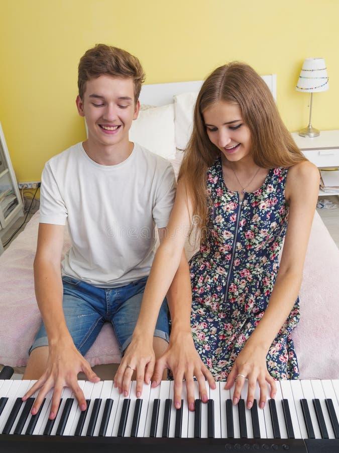 使用在电子钢琴的少年夫妇  库存图片