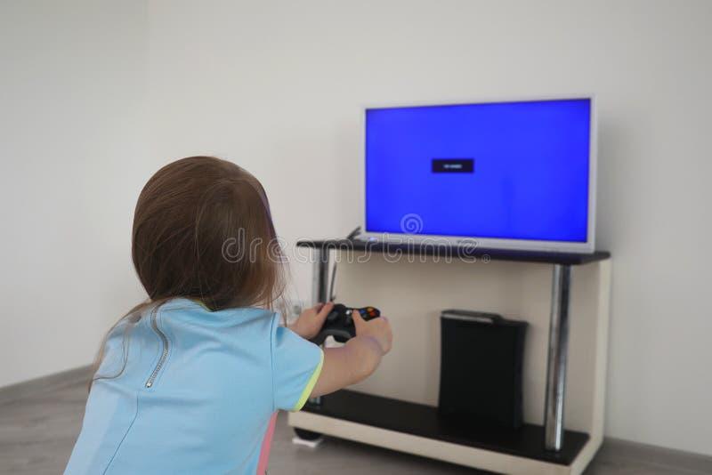 使用在电视前面的女孩 免版税图库摄影