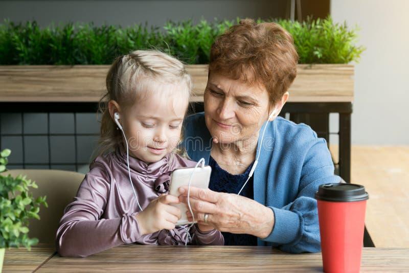 使用在电话的祖母退休和孙女 免版税库存图片