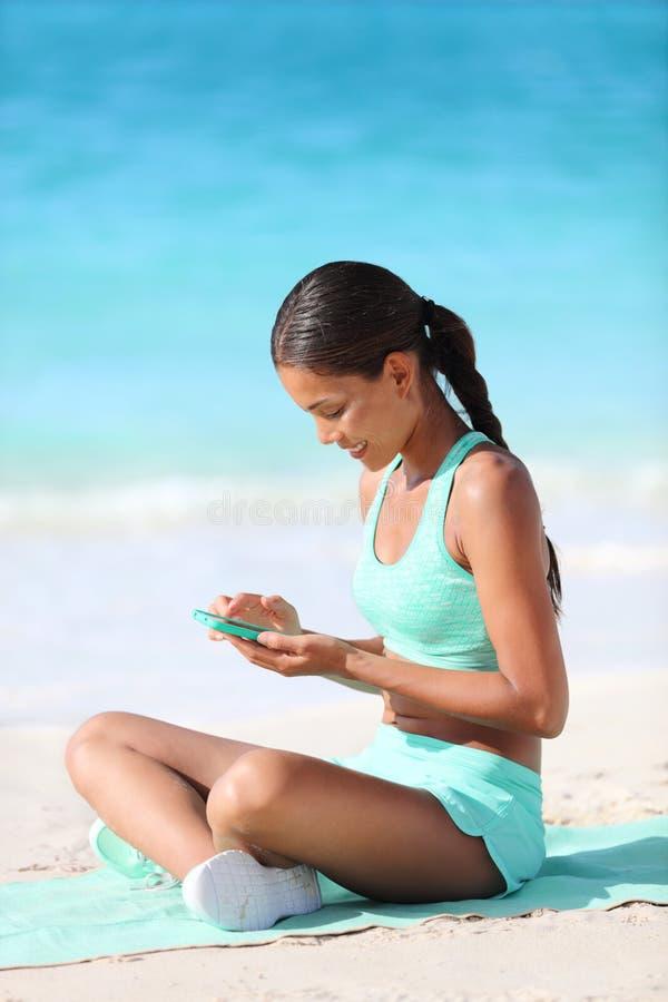 使用在电话的适合的女孩健身app发短信在海滩的旅行假日期间 免版税库存照片