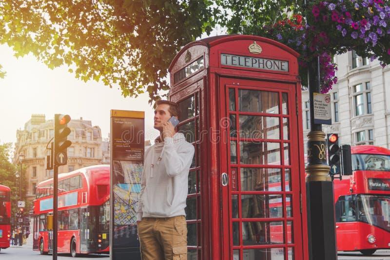 使用在电话箱子和一辆红色公共汽车前面的年轻男孩智能手机在伦敦 免版税库存图片