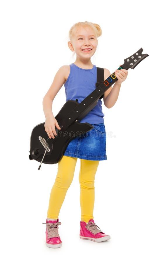 使用在电镀吉他的逗人喜爱的小女孩 免版税库存图片
