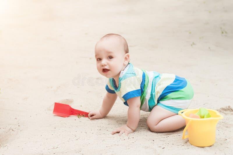 使用在白色沙子的一个小男孩 有玩具的孩子sa的 免版税库存图片
