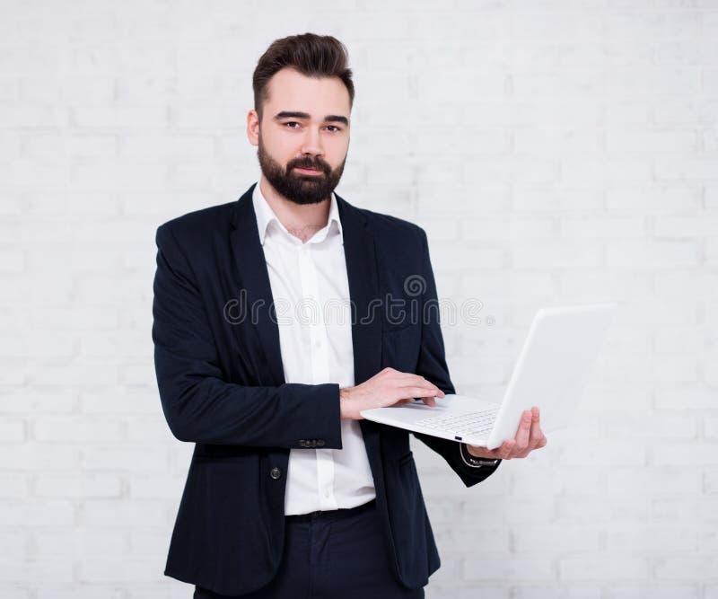 使用在白色砖墙的年轻有胡子的商人计算机 库存照片