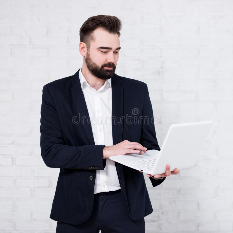 使用在白色砖墙的年轻西班牙商人膝上型计算机 免版税库存图片