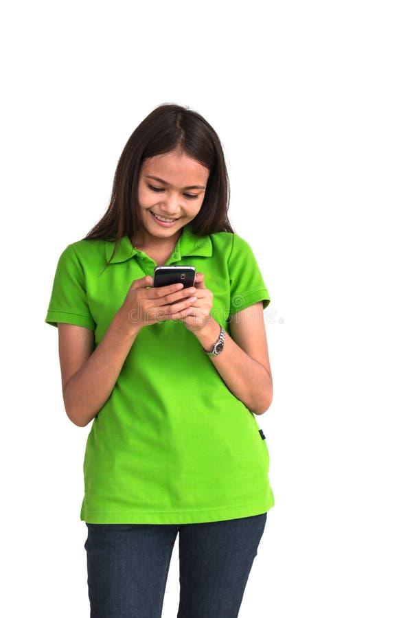 使用在白色背景的美丽的女孩巧妙的电话 免版税库存照片
