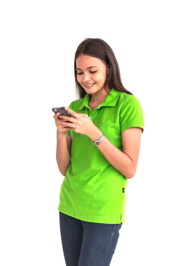 使用在白色背景的美丽的女孩巧妙的电话 图库摄影