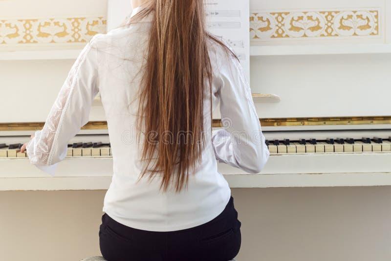 使用在白色钢琴的女孩 从女孩si的后面一个看法 免版税图库摄影