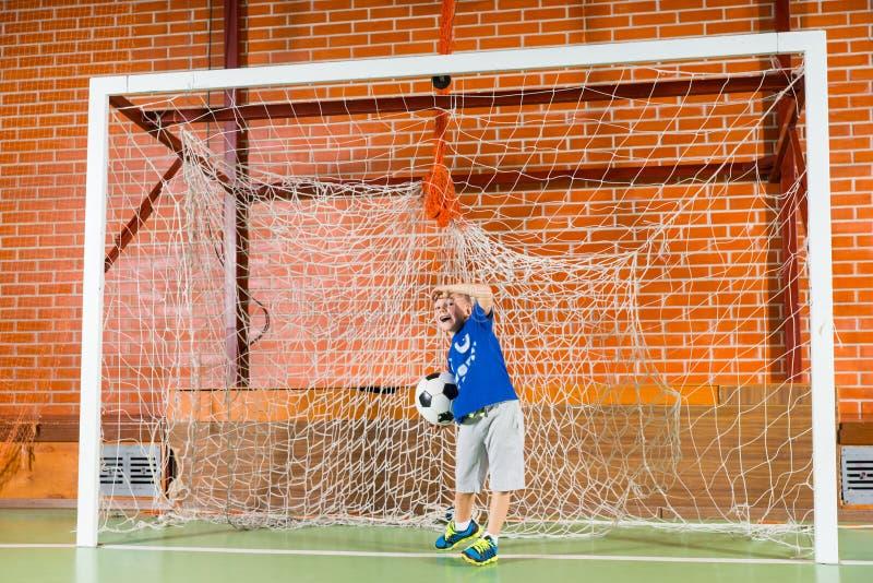 使用在目标的小男孩在足球 免版税库存照片