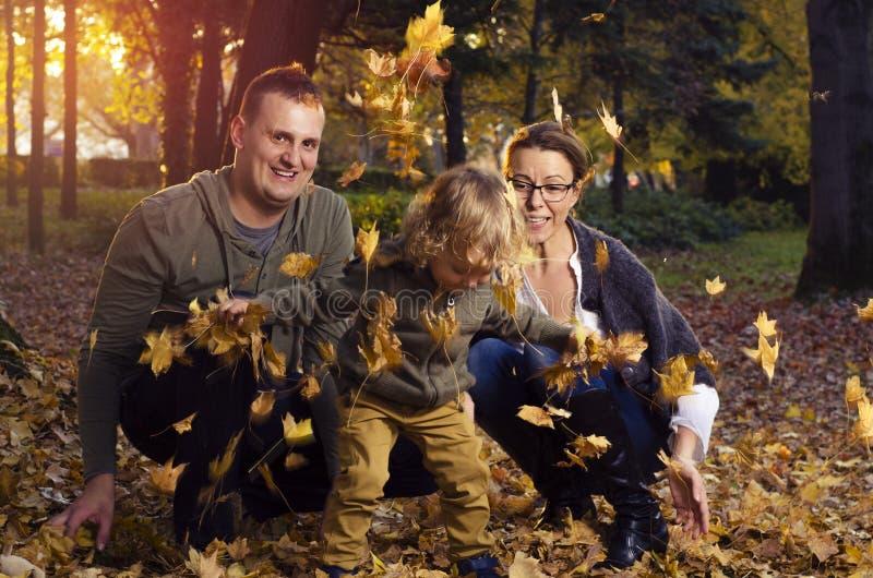 使用在秋叶的家庭 免版税库存照片