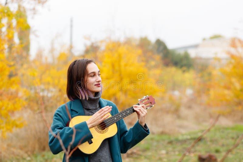 使用在秋季森林背景的尤克里里琴的一个深色的女孩 库存照片