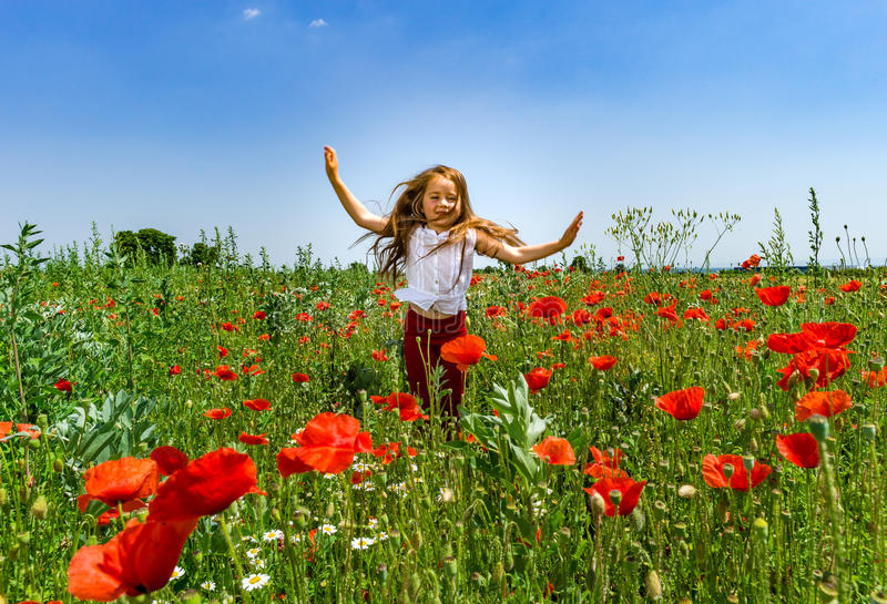 使用在红色鸦片的逗人喜爱的小女孩调遣夏日,秀丽 免版税库存图片