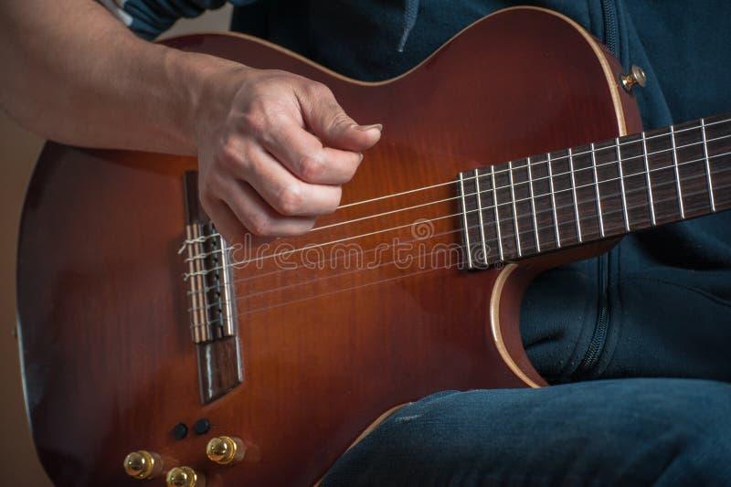 使用在经典吉他的人反对银色背景 弹吉他的英俊的年轻人 库存照片